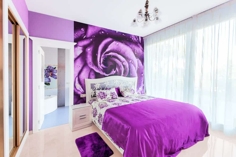 Primary bedroom boasting a stunning purple flower wall design at the back of the room's beautiful purple bed setup. The room has its own bathroom and walk-in closet too.