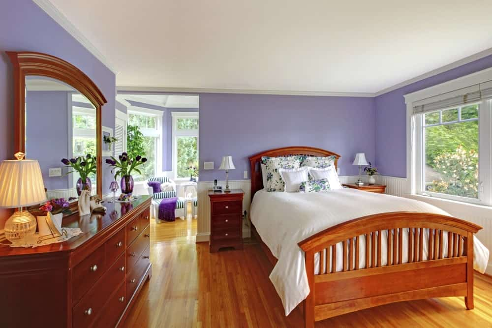 Primary bedroom with hardwood floors and purple walls. The room has a classy bed setup. The room also has its own persona living space.