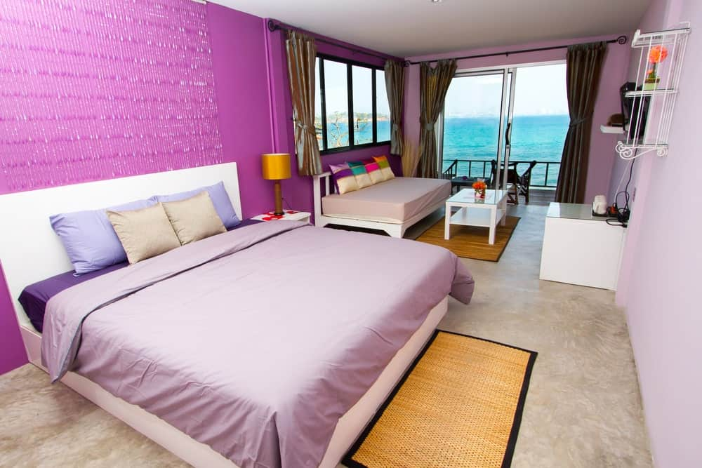 Large primary bedroom with a large bed setup along with a sofa bed on the side. The room has gorgeous carpet flooring and a purple wall. The room also offers a private terrace area overlooking the peaceful ocean view.