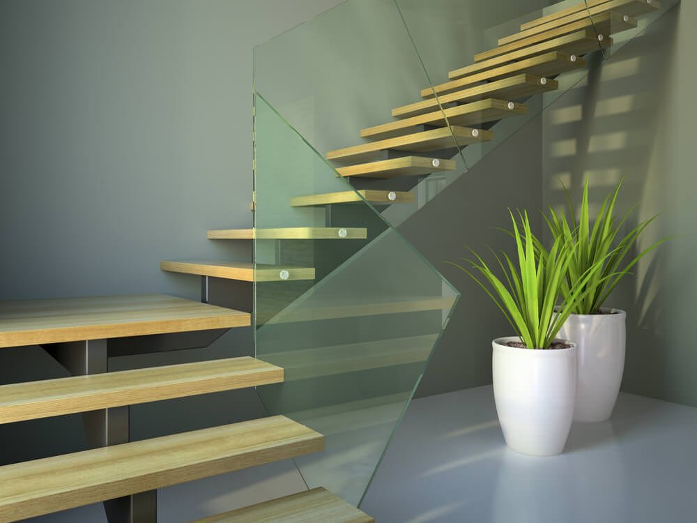 A focused shot at this home's contemporary quarter-turn staircase with hardwood steps and stylish glass railings, surrounded by gray walls.