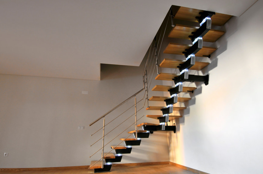 A focused shot at this home's stunning quarter-turn staircase with stylish floating steps made of hardwood.