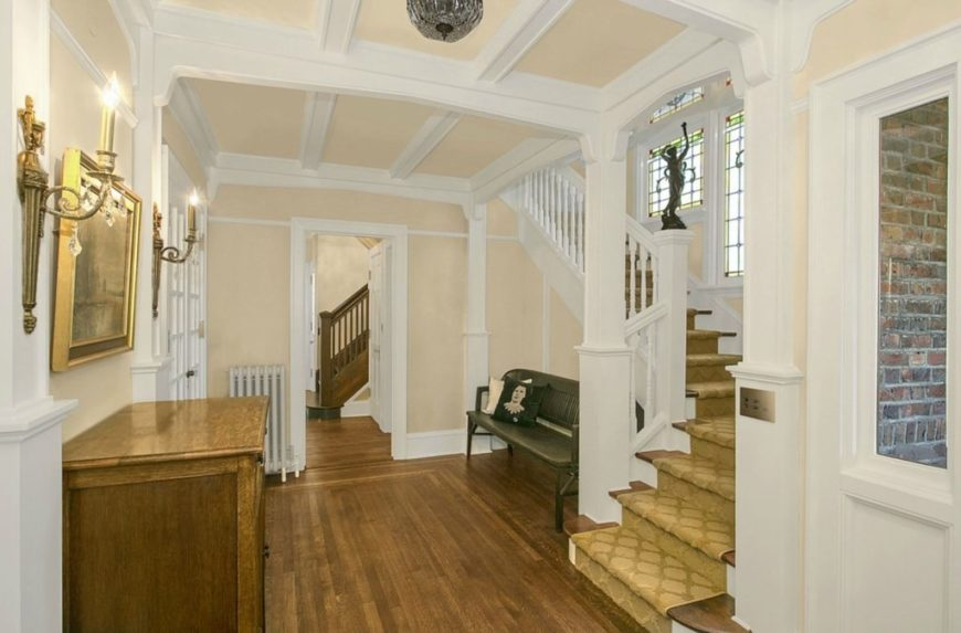 A home's hallway featuring beige walls and hardwood floors. It offers a quarter-turn staircase featuring white railings and hardwood steps covered by brown carpet.