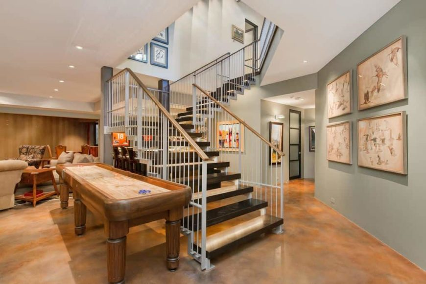 A close up look at this quarter-turn staircase with stylish steps and iron railings. The home features brown tiles floors and light gray walls with artistic wall decors.