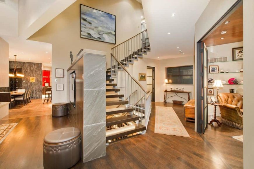 A gorgeous modern foyer leading to the dining kitchen and living space. There's a staircase with hardwood steps and iron railings.