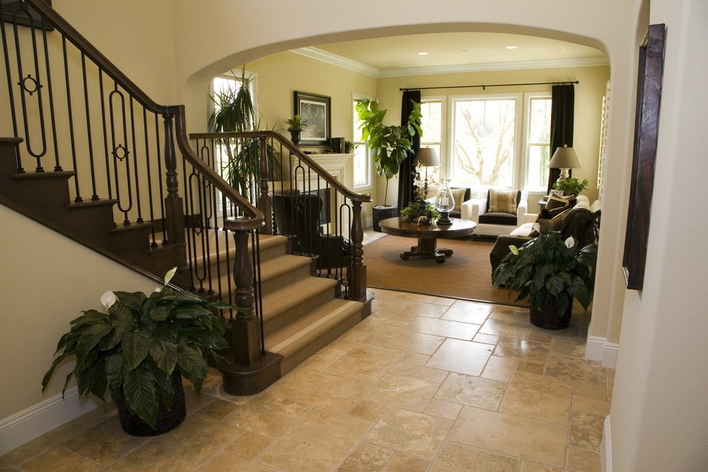 A foyer featuring a quarter turn staircase with hardwood steps covered with carpet. This entry leads straight to the home's living space with a cozy sofa set and a fireplace.