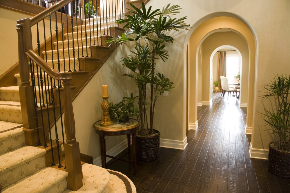 A Mediterranean house boasting hardwood floors. It offers a quarter-turn staircase featuring classy carpeted steps and hardwood handrails.