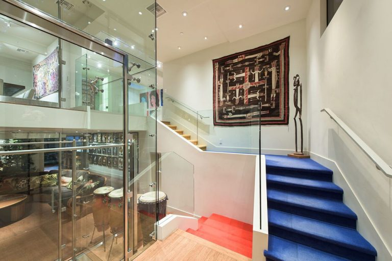 This home boasts a stunning foyer featuring a staircase with blue carpet steps and glass railings, lighted by scattered recessed ceiling lights.