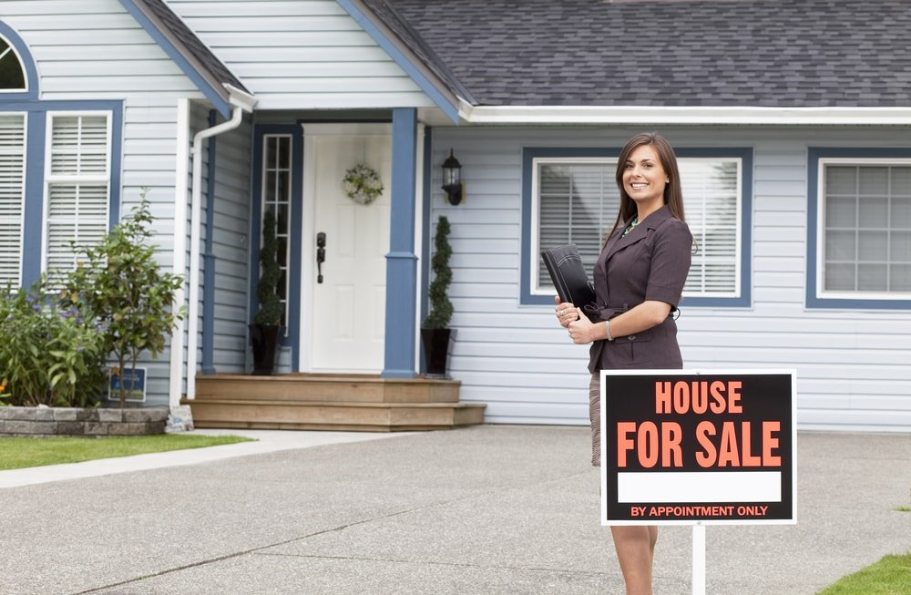 A real estate professional stands outside a house for sale.