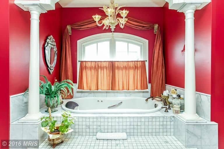 This primary bathroom featuring a white drop-in soaking tub on a tiles platform lighted by a charming chandelier and is surrounded by red walls.