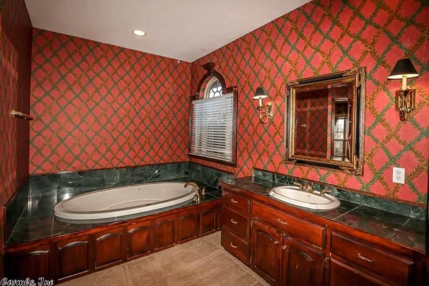 Primary bathroom with decorated red walls surroundings the room. This bathroom offers a drop-in tub with black tiles, along with a sink counter with a black tiles countertop.