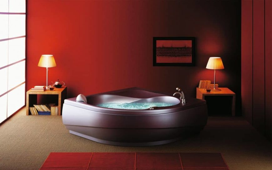 Modern primary bathroom with a modern bathtub surrounded by red walls and lighted by two table lamps. The room has carpeted flooring topped by a red area rug.