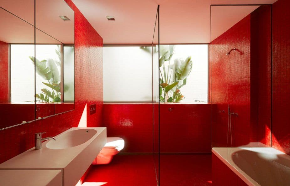 Primary bathroom featuring red tiles walls and red floors. It offers a red and white freestanding tub, a floating vanity sink counter, and a walk-in shower area.