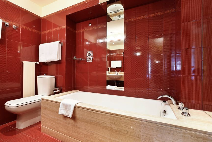 A focused shot at this primary bathroom's drop-in soaking tub and a toilet at the edge, surrounded by red tiles walls and floors.