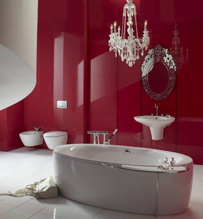Primary bathroom featuring a large freestanding soaking tub, a floating sink with an elegant mirror, and a gorgeous white chandelier lighting up the space surrounded by red walls.
