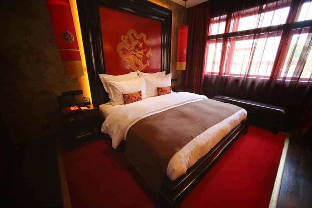 Asian-style master bedroom featuring an elegant bed setup with a dragon-designed headboard. The room features red window curtains and hardwood flooring topped by a red area rug.