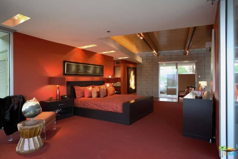 Large master bedroom with red walls and red carpet flooring. It offers a large cozy bed and has its own bathroom too.