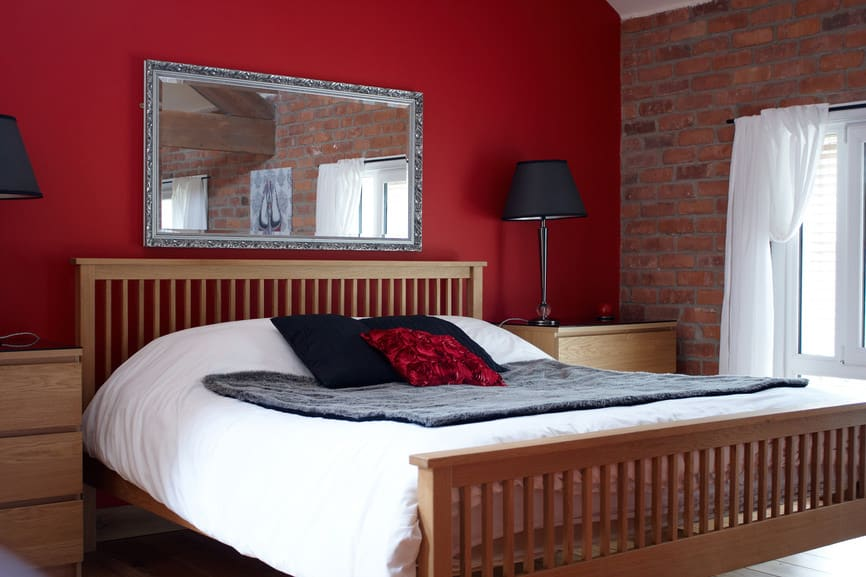 A focused shot at this master bedroom's large bed with a wooden frame lighted by black table lamps on both sides. The room features a concrete red wall and a red brick wall.