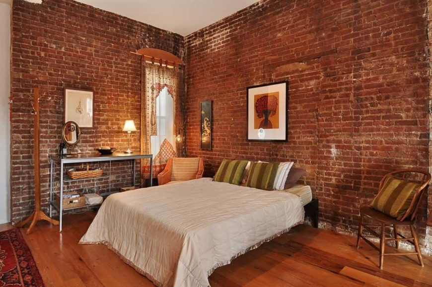 A master bedroom with a nice bed surrounded by red brick walls. The room also features hardwood flooring.
