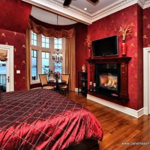 A primary bedroom with red decorated walls and an elegant red velvet bed setup with a fireplace and a TV set in front. The room features a sitting area by the windows and a balcony area.