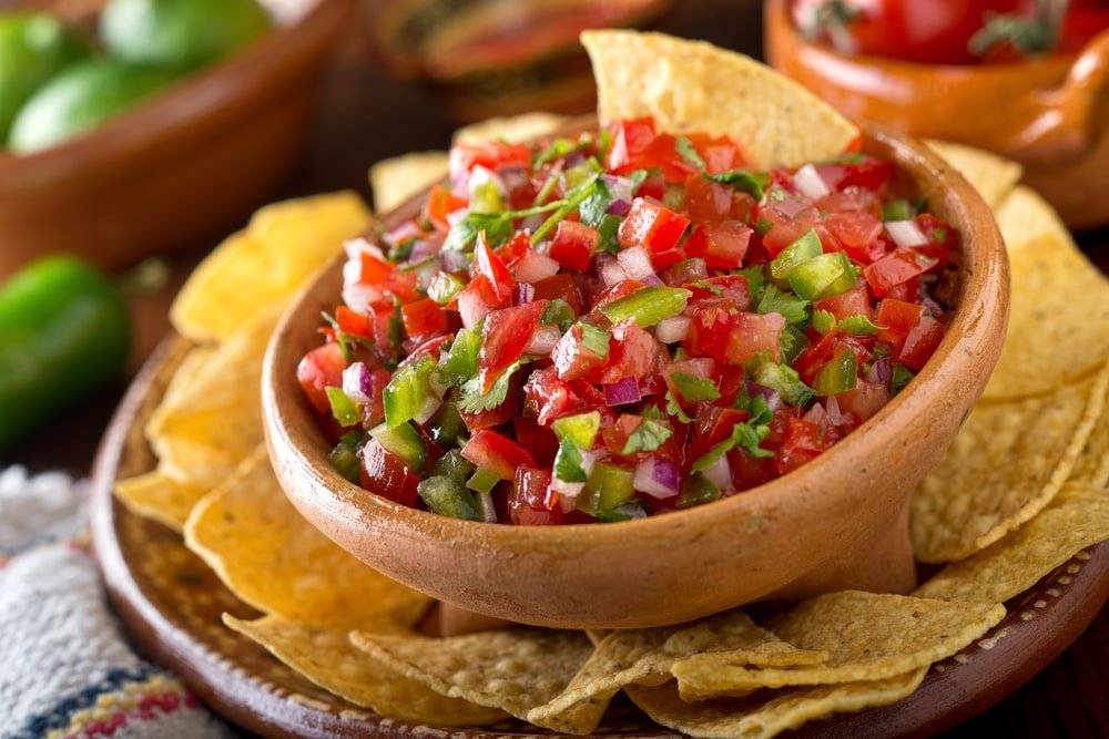 Salsa on a bowl surrounded by nachos.