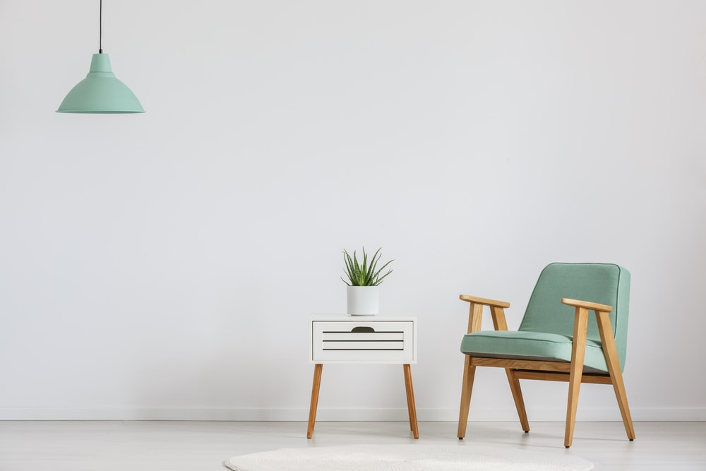 Minimalist sitting area with a small cupboard and a pair of mint pendant lighting and accent chair.