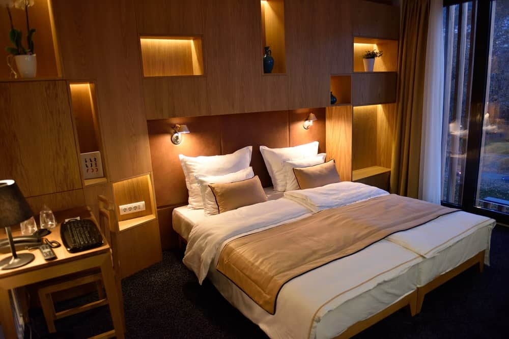 A focused shot at this primary bedroom's large bed lighted by wall lights. The room has brown walls with built-in shelving.