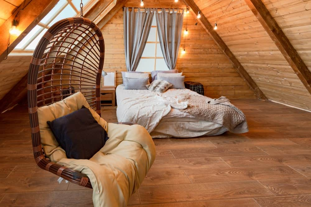 Primary bedroom boasting a comfy bed and a gorgeous swing, surrounded by wooden walls and ceiling, along with hardwood flooring.