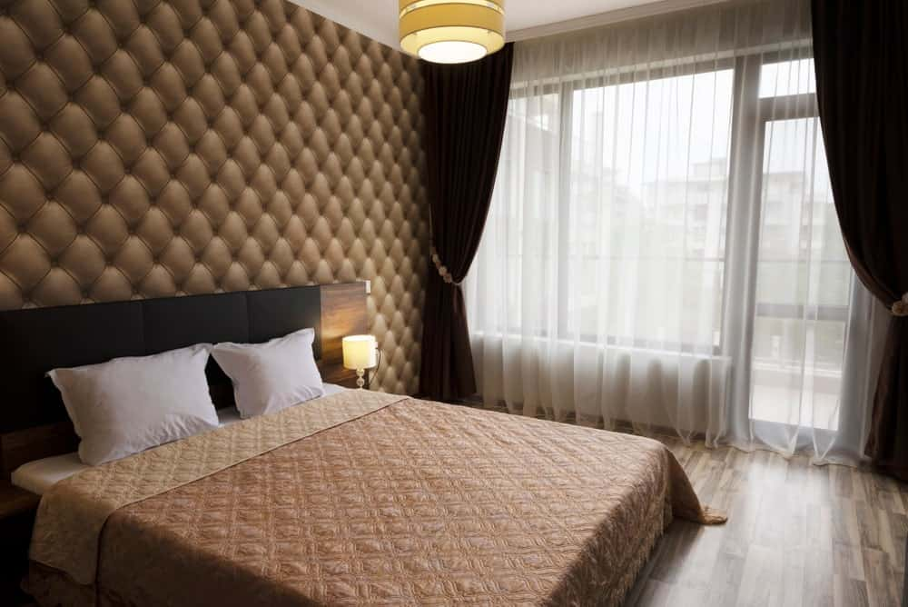 Primary bedroom boasting a luxurious wall and a classy bed. The room offers lovely window curtains and stylish hardwood flooring.