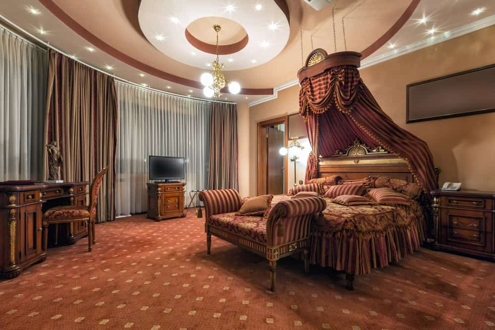 A spacious primary bedroom boasting elegant brown carpet flooring along with a stunning custom ceiling. The room offers a large brown bed that looks absolutely luxurious.
