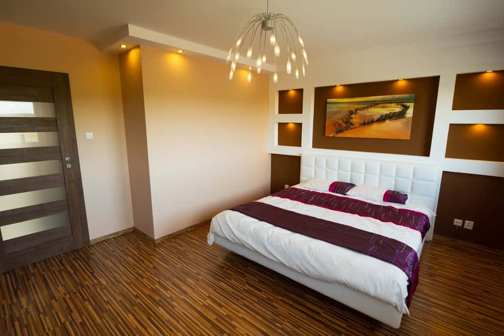 Primary bedroom with stylish flooring and a regular ceiling lighted by magnificent ceiling lighting. The room offers a lovely white bed with a stylish wall behind.