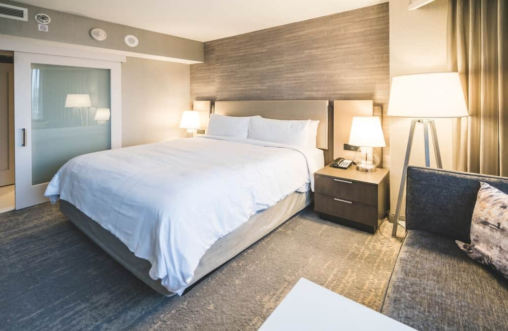 This primary bedroom features a modish bed set lighted by lovely table lamps on bedside tables. The room has stylish flooring and a gray couch on the side.