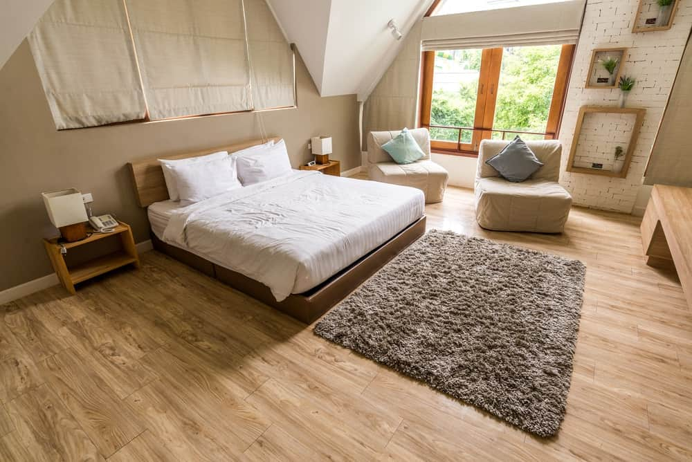 A spacious primary bedroom featuring hardwood floors and brown walls, along with a custom ceiling. The room offers a large cozy bed.