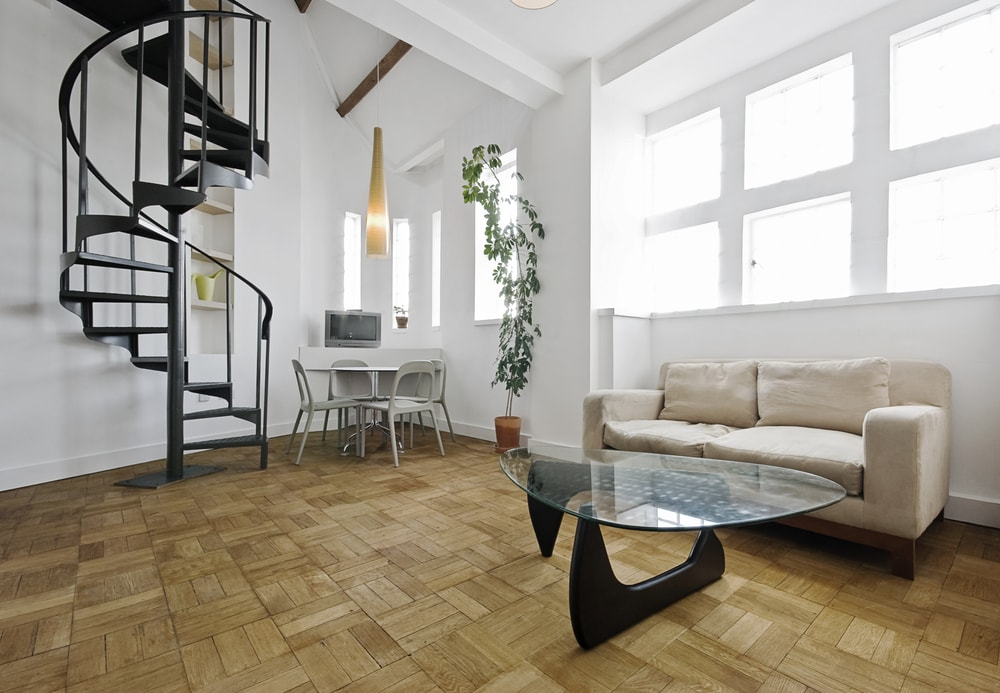 A spacious living space boasting stylish hardwood flooring and white walls. The area also has a stylish black spiral staircase.