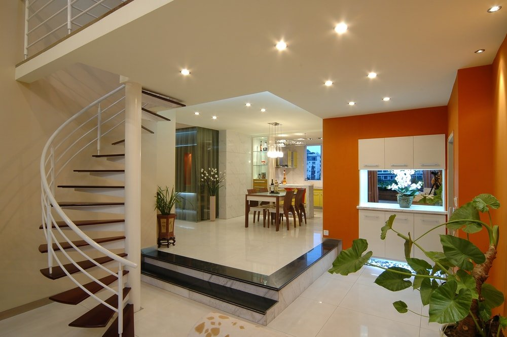A modern house featuring tiles flooring and white and orange walls, along with a white ceiling lighted by recessed lights. The home also features a spiral staircase.
