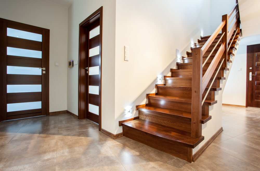 A modern home featuring stylish flooring and a tall ceiling. The area features a gorgeous staircase with hardwood steps and hardwood railings.