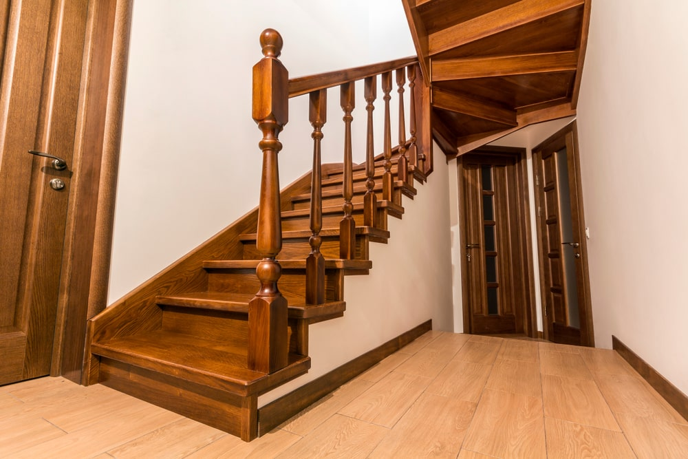 A focused shot at this home's staircase boasting hardwood steps and hardwood railing and handrail.