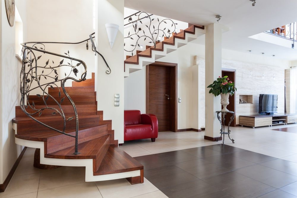 A spacious foyer boasting a gorgeous staircase with elegantly-designed railings. The home features tiles flooring and white walls.