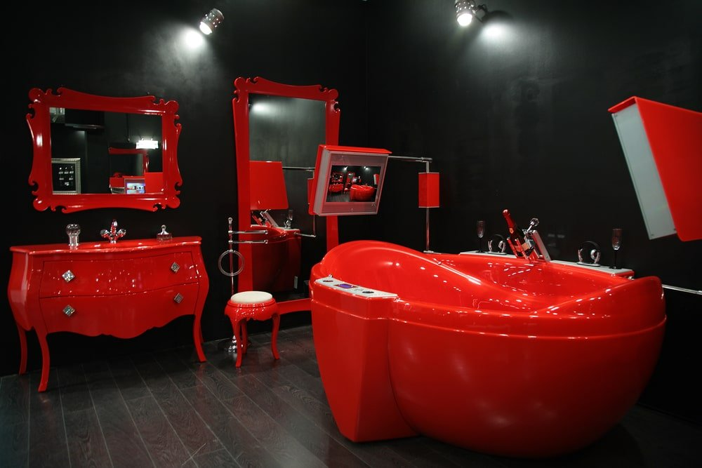 A stunning primary bathroom featuring black walls and white lights, along with hardwood flooring. The room offers a set of red furniture such as red bathtub, a red sink counter and red mirrors.