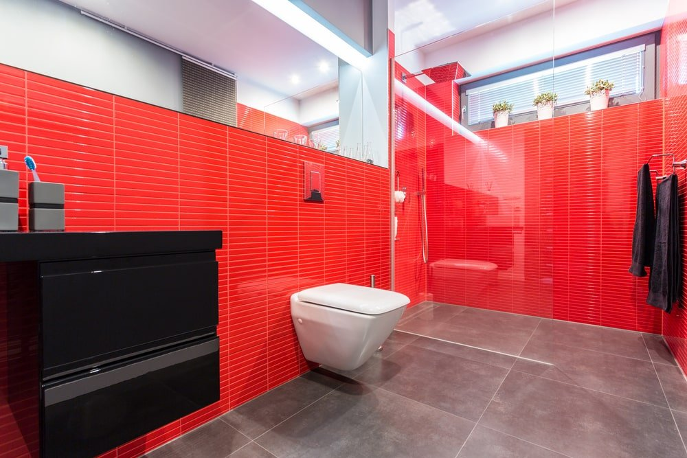 A spacious primary bathroom featuring red walls and large gray tiles flooring. The room has a walk-in shower and a black sink counter under the room's tall ceiling.