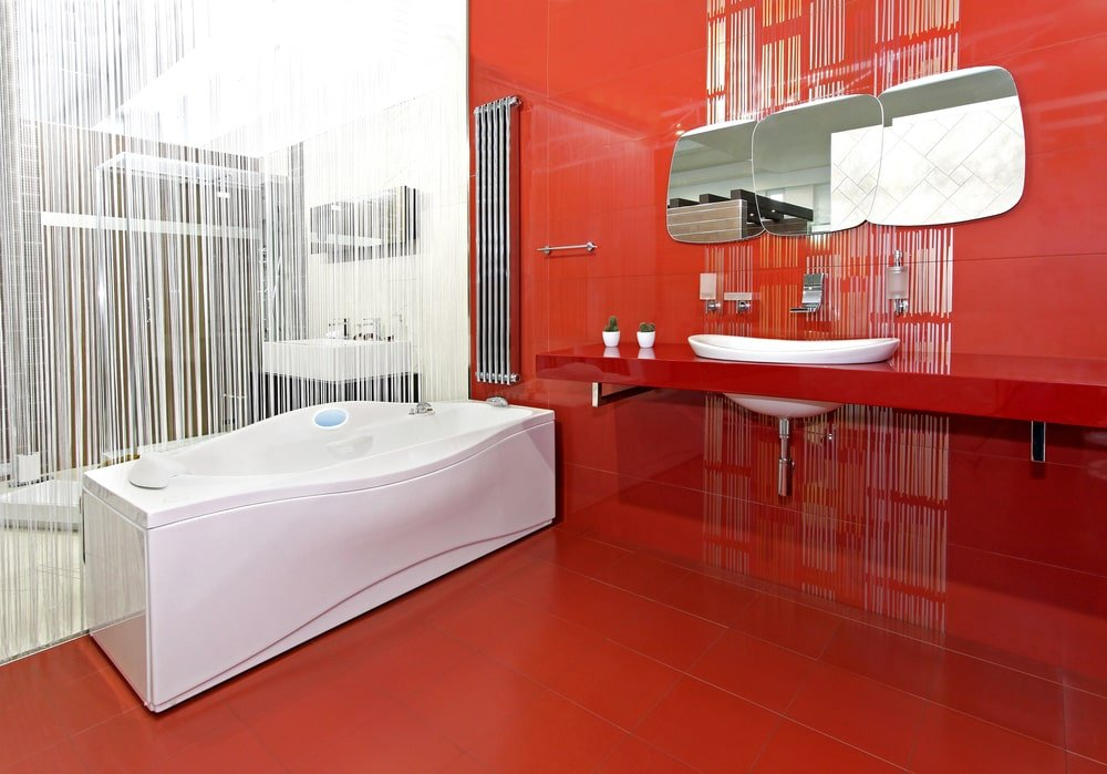 Primary bathroom boasting red tiles walls and floors, along with a red floating vanity sink counter. The room also has a white freestanding deep soaking tub.