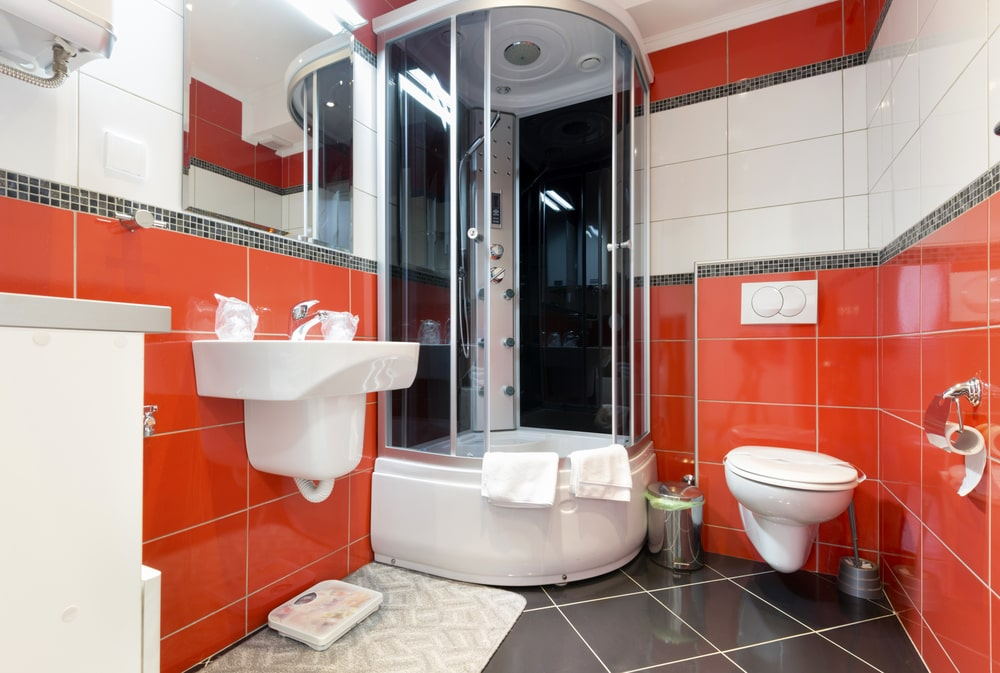 This bathroom offers a walk-in shower booth and a floating sink, along with red and white walls with dark gray tiles flooring.