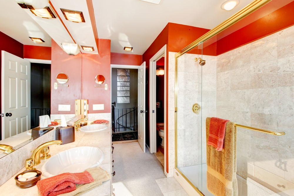 Primary bathroom with a red and white color scheme with a gold tone. The room features a sink counter with two sinks and has a walk-in shower room along with a toilet room.