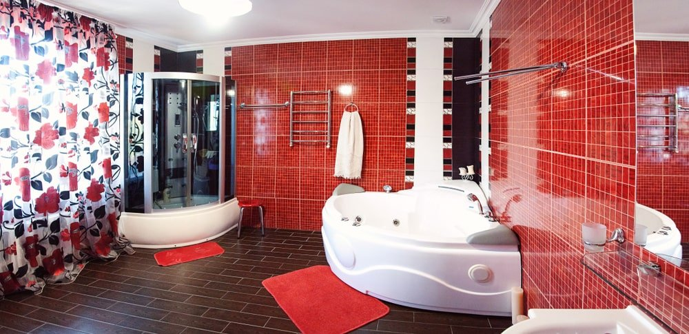 Spacious primary bathroom featuring red tiles walls and a white ceiling. The room offers a walk-in corner shower booth and a large white soaking tub.