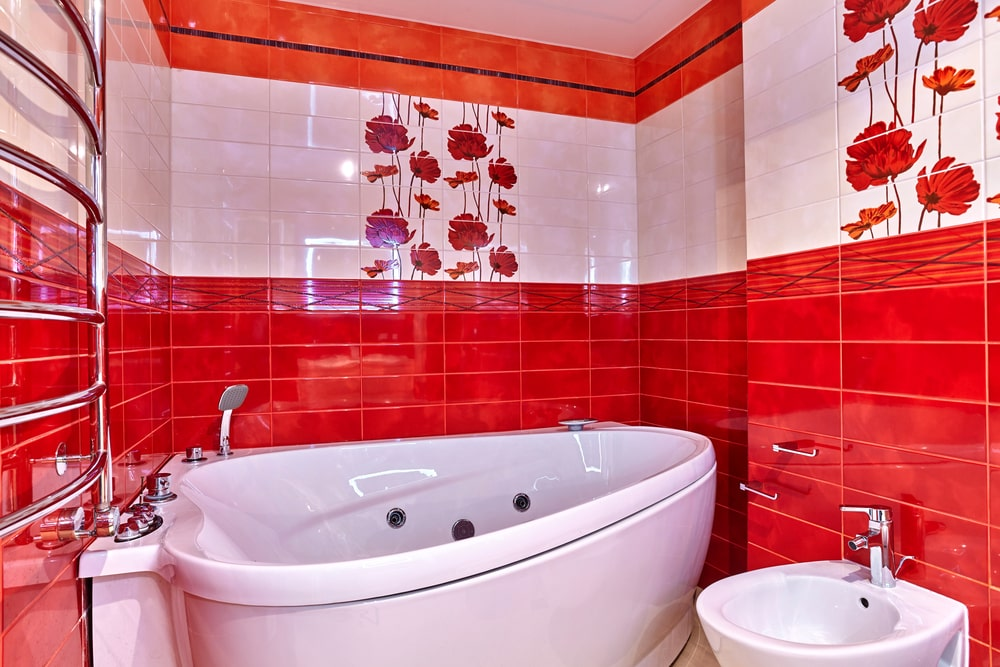 A focused shot at this bathroom's large corner deep soaking tub surrounded by red and white flower-decorated walls.