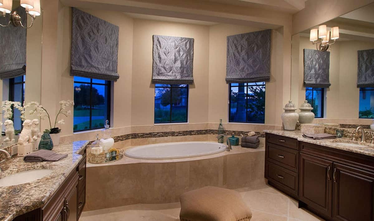 This elegant primary bathroom has two vanities on opposite walls with dark brown wooden cabinetry to complement the earthy beige tone of the rest of the bathroom. These lead to a large bathtub inlaid by the curved row of window at the far end.