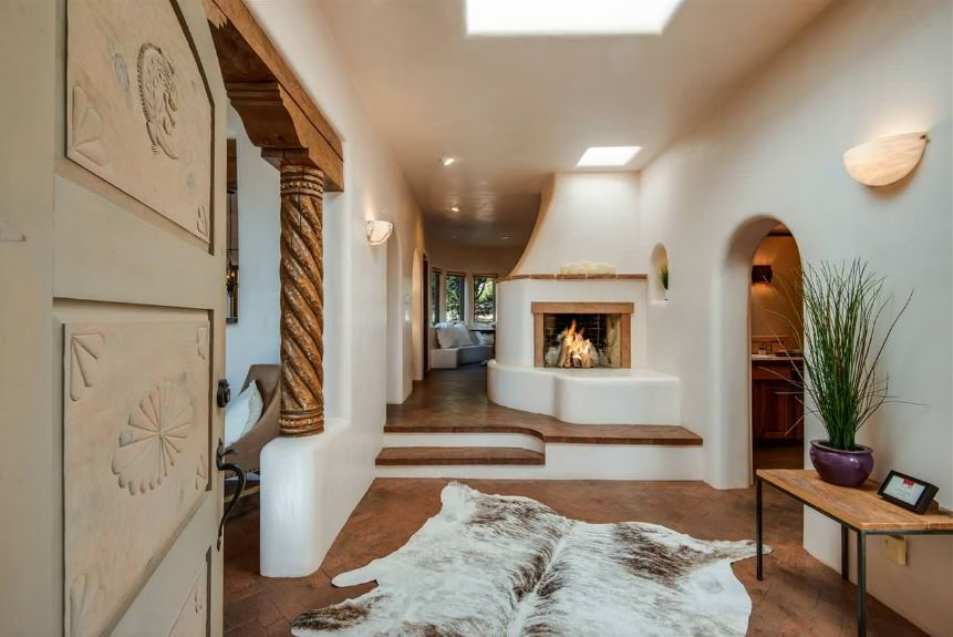 The beautiful carvings of the wooden main door sets the theme of this Southwestern-style foyer with a large animal fur area rug on the terracotta floor that pairs well with the warmth of the fireplace facing the entryway.
