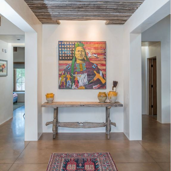 This beautiful Southwestern-style foyer is adorned with a colorful painting of a Native American Indian with an American flag in the background. This serves as a nice dash of color for the white walls and the wooden console table underneath.