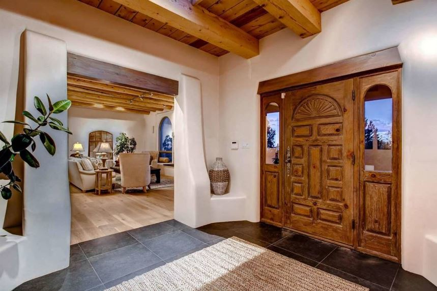 The wooden main door of this Southwestern-style foyer has an elegant and classic finish to it that matches well with the two side lights flanking it with glass panels. This is also matched by the wooden ceiling that has exposed wooden beams complementing the light beige walls with built-in alcoves.