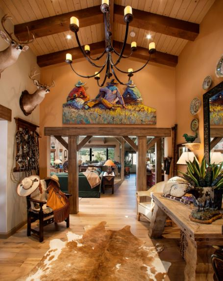 This awesome sit of the Southwestern-style foyer will welcome you upon entry. There is a wooden entryway on the far side that looks like it came from an old mine. This is topped with a colorful painting of cowboys. This pairs well with the various decors of the beige walls.
