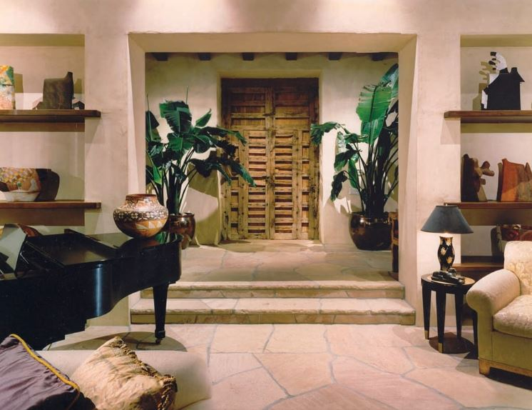 The two potted plants stand out against the off-white walls as they flank the wooden main door that has a unique design to it. This Southwestern-style foyer has the same irregular stone flooring as the rest of the home that has a grand piano by the entrance.